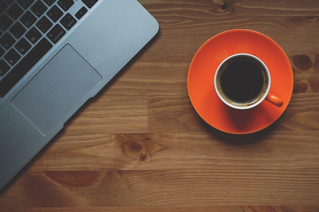 tasse de café sur bureau et ordinateur